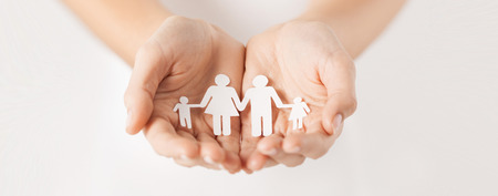 close up of woman cupped hands showing paper man family