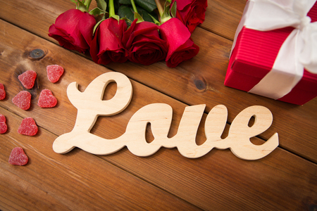attentions: romance, valentines day and holidays concept - close up of word love, gift box, red roses and heart-shaped candies on wood