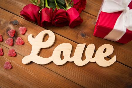 uprzejmości: romans, Walentynki i święta koncepcji - bliska słowo miłość, pudełko, czerwonych róż i kształcie serca cukierki na drewnie Zdjęcie Seryjne
