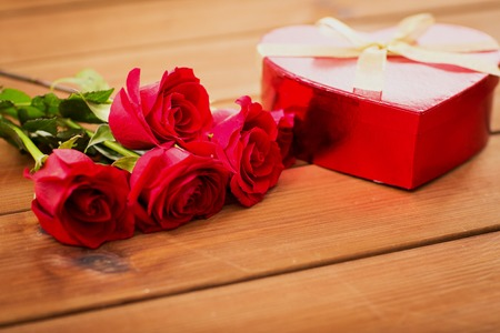 flirtation: love, date, romance, valentines day and holidays concept - close up of heart shaped gift box and red roses on wooden table