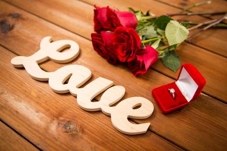 uprzejmości: Propozycja, romans, Walentynki i święta pojęcie - zamknąć pudełko z pierścionek zaręczynowy diament, czerwonych róż i słowo miłość na drewno Zdjęcie Seryjne