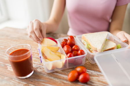 envases plasticos: healthy eating, storage, dieting and people concept - close up of woman with food in plastic container at home kitchen