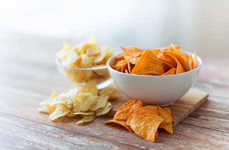 junkfood: fast food, junk-food, cuisine and unhealthy eating concept - close up of crunchy potato crisps and corn crisps or nachos in bowls Stock Photo