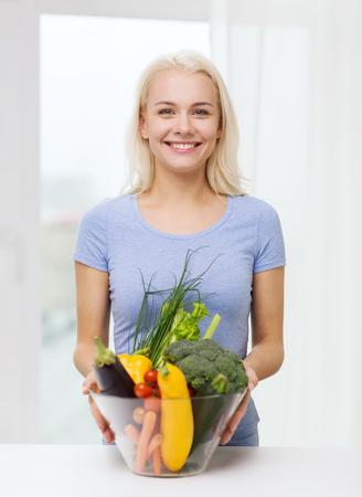 una alimentación sana, comida vegetariana, la dieta y el concepto de la gente - sonriente mujer joven con plato de verduras en el hogar