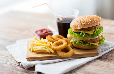 fast food and unhealthy eating concept - close up of hamburger or cheeseburger, deep-fried squid rings, french fries, drink and ketchup on wooden table 版權商用圖片