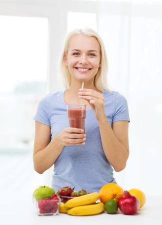 cocteles de frutas: una alimentación sana, comida vegetariana, la dieta y el concepto de la gente - la mujer sonriente beber batido de frutas a partir de vidrio en el hogar Foto de archivo