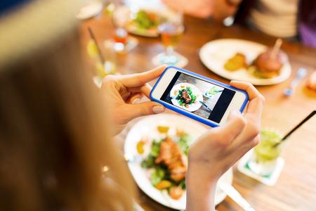 la gente, el ocio, la tecnología y la adicción a Internet concepto - cerca de la mujer con el teléfono inteligente fotografiar comida en el restaurante