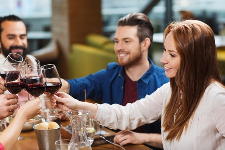 leisure, celebration, food and drinks, people and holidays concept - smiling friends having dinner and drinking red wine at restaurant Stock Photo