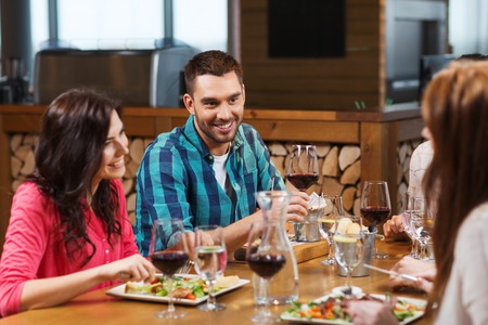 restaurant dining: leisure, eating, food and drinks, people and holidays concept - smiling friends having dinner and drinking red wine at restaurant Stock Photo