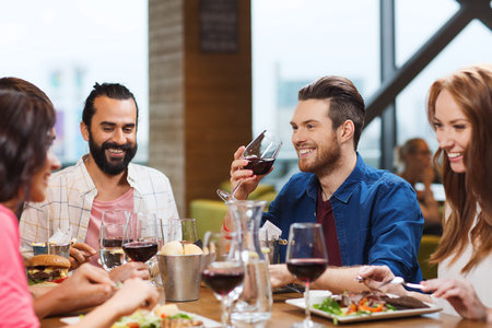 lifestyle dining: leisure, eating, food and drinks, people and holidays concept - smiling friends having dinner and drinking red wine at restaurant Stock Photo