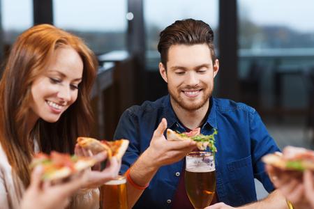 italienisches essen: Freizeit, Essen und Getränke, die Menschen und Ferien-Konzept - lächelnde Freunde Pizza und Bier trinken im Restaurant oder Pub Essen
