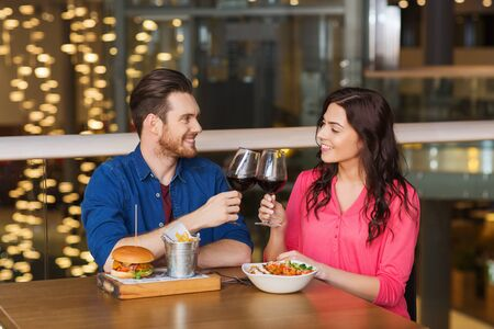 food and wine: leisure, celebration, food and drinks, people and holidays concept - smiling couple having dinner and drinking red wine at date in restaurant