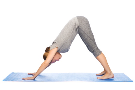 dog pose: fitness, sport, people and healthy lifestyle concept - woman making yoga in downward facing dog pose on mat Stock Photo