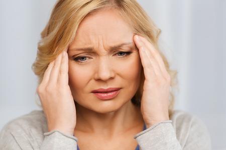 dolor de cabeza: las personas, la salud, el estr�s y el concepto de problema - infeliz mujer que sufre de dolor de cabeza en el hogar Foto de archivo