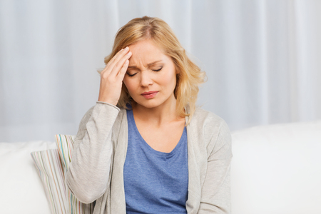 people, healthcare, stress and problem concept - unhappy woman suffering from headache at home