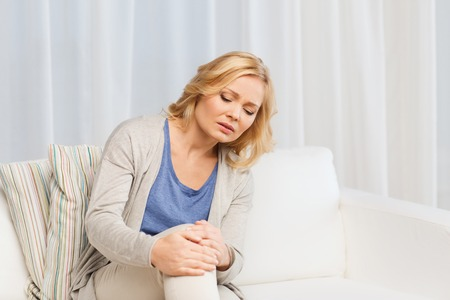 stifle: people, healthcare and problem concept - unhappy woman suffering from pain in leg at home Stock Photo