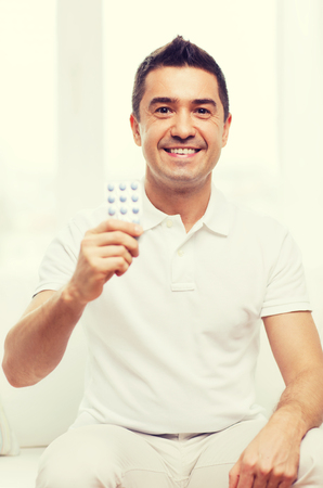 home health care: people, medication, medicine and health care concept - happy man showing pack of pills at home