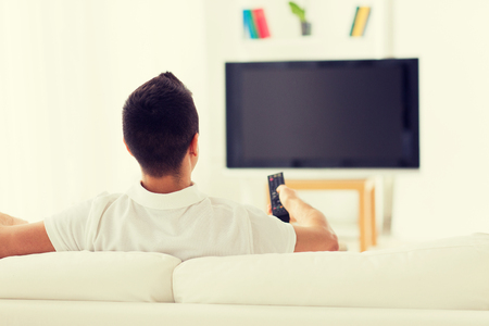 leisure, technology, mass media and people concept - man watching tv and changing channels at home from back Stock Photo
