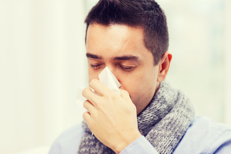 gripe: cuidado de la salud, la gripe, las personas, la rinitis y el concepto de la medicina - Cerca del hombre enfermo que sopla su nariz con la servilleta de papel en casa