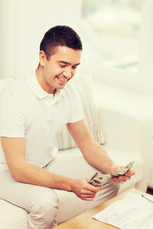 business savings: business, savings, finances, income and people concept - man with papers and calculator at home