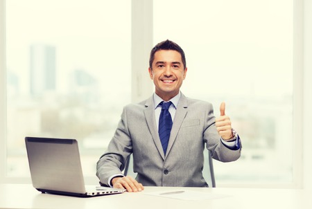 businessman in office: business, people and technology concept - smiling businessman in suit working with laptop computer in office