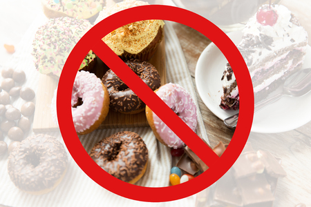 fast food, low carb diet, fattening and unhealthy eating concept - close up of glazed donuts, cakes and chocolate sweets behind no symbol or circle-backslash prohibition sign