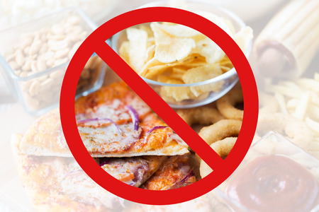 no food: fast food, low carb diet, fattening and unhealthy eating concept - close up of pizza, potato chips and other snacks behind no symbol or circle-backslash prohibition sign