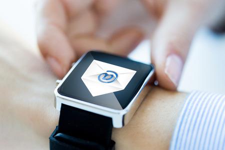 ビジネス、技術、通信、接続、人々 の概念 - はスマートウォッチにメール アイコンが付いている手のクローズ アップ