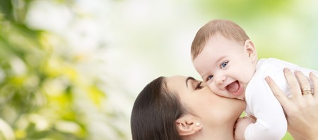 family, motherhood, children, parenthood and people concept - happy mother kissing her baby over green natural background Stockfoto