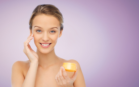 skin care woman: beauty, people, cosmetics, skincare and cosmetics concept - happy young woman applying cream to her face over violet background Stock Photo