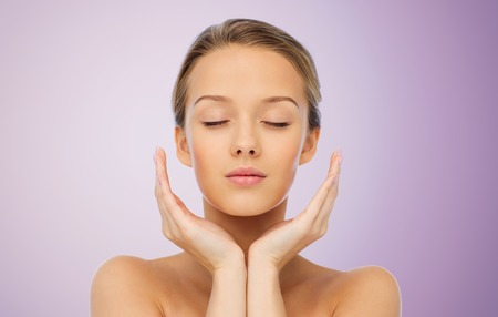 caras: belleza, gente, cuidado de la piel y el concepto de salud - mujer joven rostro y las manos sobre el fondo violeta