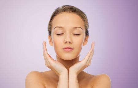 Schönheit, Menschen, Hautpflege und Gesundheit Konzept - junge Frau Gesicht und Hände über violettem Hintergrund