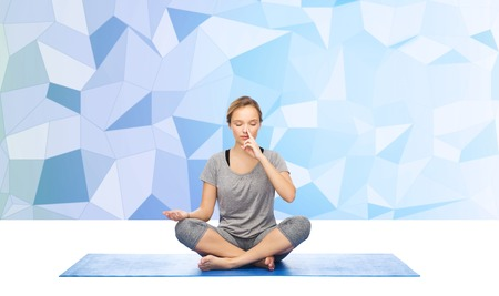 pranayama: fitness, sport, people and healthy lifestyle concept - woman making yoga meditation in lotus pose on mat over blue polygonal background Stock Photo