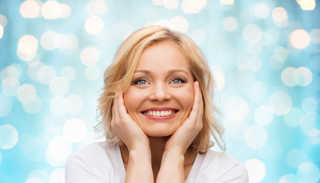 middle age: beauty, people and skincare concept - smiling middle aged woman in white shirt touching face over blue holidays lights background