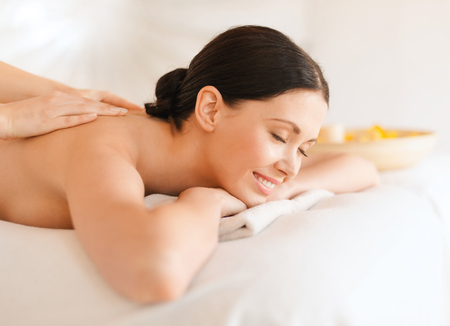 beautiful body: health and beauty, resort and relaxation concept - woman in spa salon getting massage Stock Photo