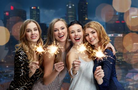 diciembre: fiesta, días de fiesta, la vida nocturna y el concepto de las personas - mujeres jóvenes felices bailando en la discoteca del club de noche sobre fondo negro
