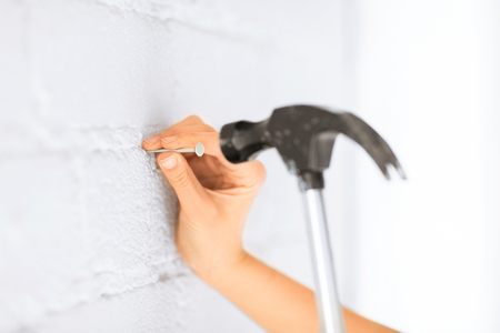 construction nails: architecture and home renovation concept - architect hammering nail in wall