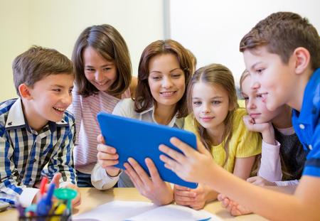 profesores: educación, escuela primaria, el aprendizaje, la tecnología y el concepto de la gente - grupo de niños de la escuela con el maestro mira al ordenador Tablet PC en el aula Foto de archivo