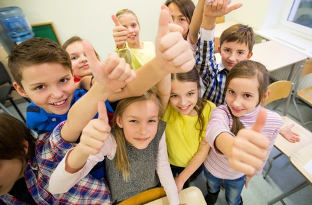 onderwijs, basisschool, leren, gebaar en mensen concept - groep schoolkinderen en zien thumbs up in de klas