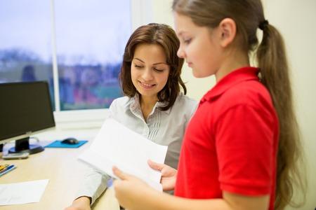 preguntando: educación, escuela primaria, el aprendizaje, la exploración y la gente concepto - Niña de la escuela con el cuaderno y el profesor en el aula Foto de archivo