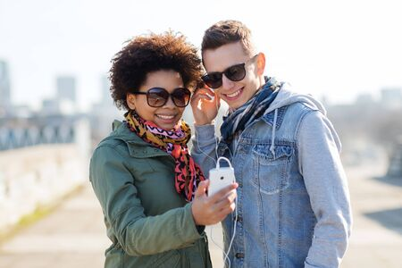 black couple: summer, technology, people and friendship concept - smiling couple with smartphone and earphones listening to music on city street