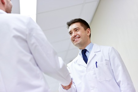 white coat: clinic, profession, people, health care and medicine concept - smiling doctors meeting and greeting by handshake at hospital corridor