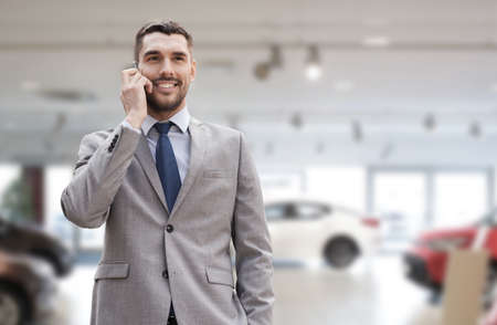 young male: auto business, car sale, gesture and people concept - smiling businessman talking on smartphone over auto show background