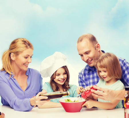 children eating: food, family, children, hapiness and people concept - happy family with two kids making dinner at home Stock Photo