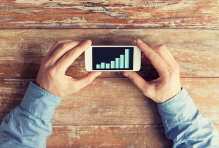business table: business, statisctics, people and technology concept - close up of male hands holding smartphone with chart on screen at table