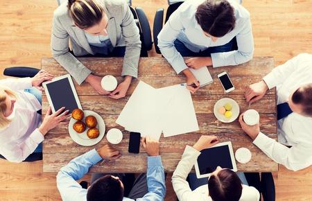 almuerzo: negocios, personas, descanso y trabajo en equipo concepto - cerca de la reunión del equipo creativo y de tomar café con magdalenas durante el almuerzo en la oficina Foto de archivo