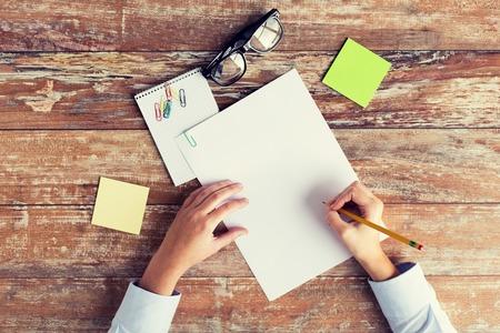 persona escribiendo: los negocios, la educación y el concepto de la gente - cerca de las manos femeninas con papeles, pegatinas y anteojos en la mesa