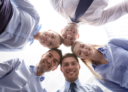 co workers: business, people and teamwork concept - smiling group of businesspeople standing in circle