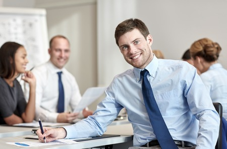 co workers: business, people and teamwork concept - smiling businessman with group of businesspeople meeting in office Stock Photo