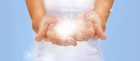people and magic concept - close up of twinkles or fairy dust on female cupped hands over blue background Stock Photo